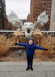 Henry poses with a winged lion sculpture on the Highline.