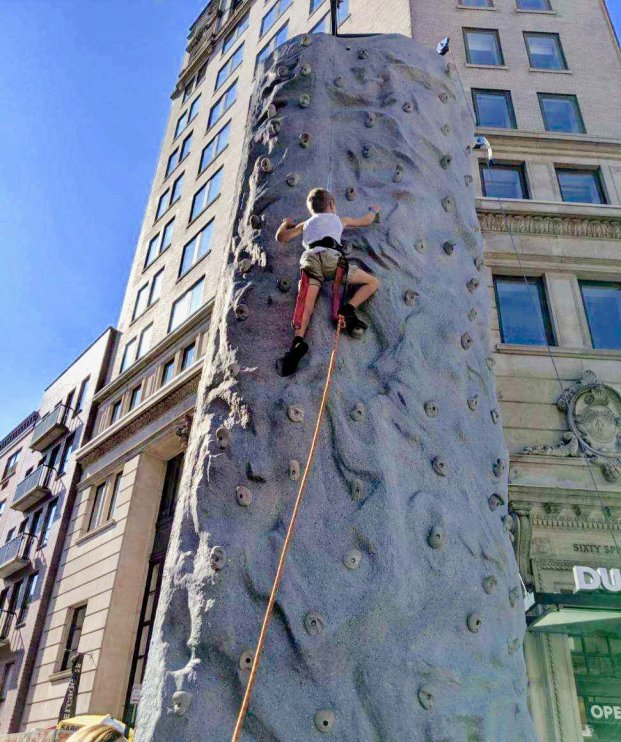 Henry on his way to the top of an outdoor climbing pillar at Summer Streets.